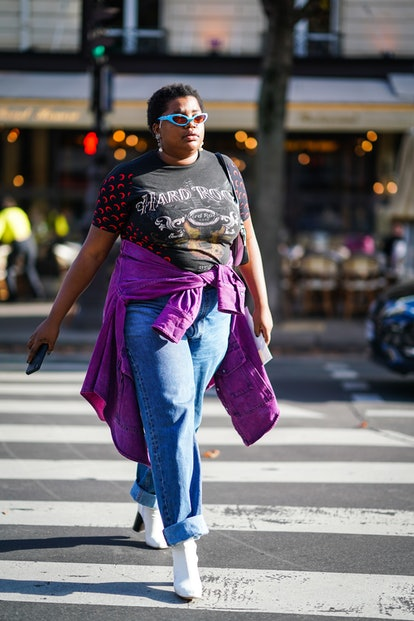 """PARIS, FRANCE - SEPTEMBER 28: A guest wears blue sunglasses, a """"Hard Rock Cafe"""" t-shirt, a purple jacket around the waist, blue denim jeans, white boots, outside CDG Comme des Garçons, during Paris Fashion Week - Womenswear Spring Summer 2020, on September 28, 2019 in Paris, France. (Photo by Edward Berthelot/Getty Images)"""