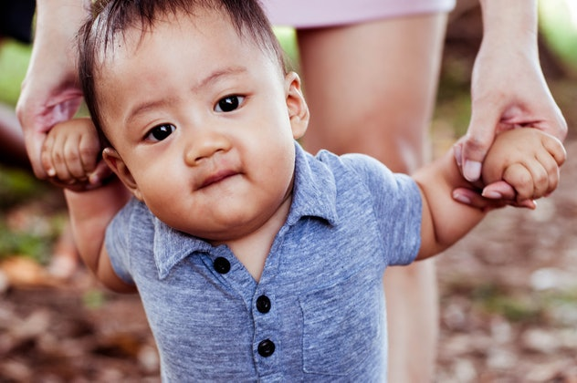 Front view of Southeast Asian baby boy learning to walk with his mother in a natural parkland