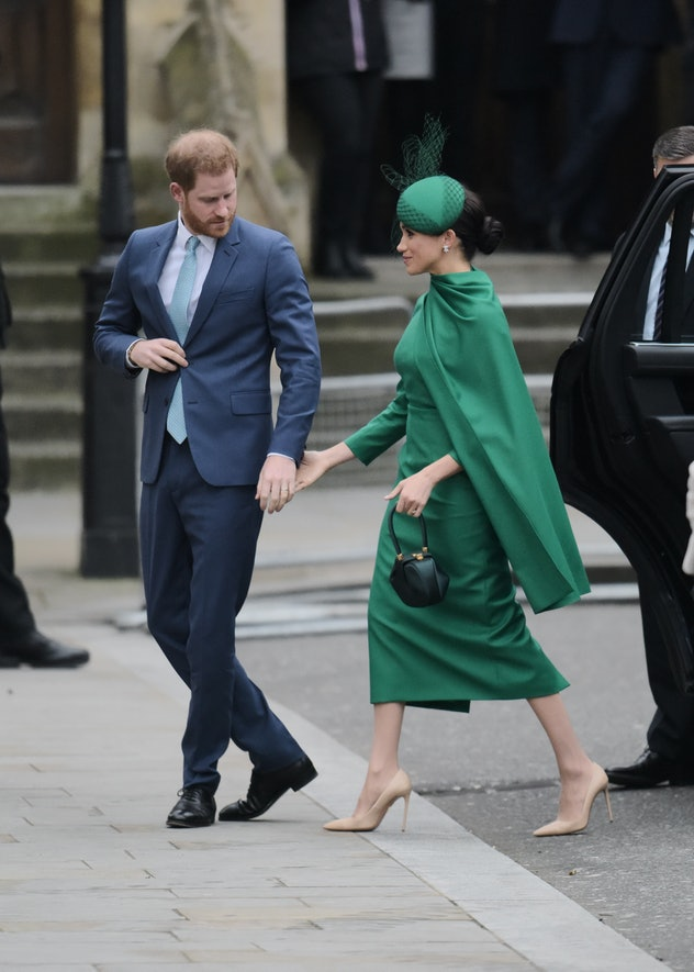Meghan Markle reaches for Prince Harry's hand.