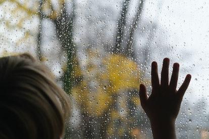 kid with hand pressed up to rainy window