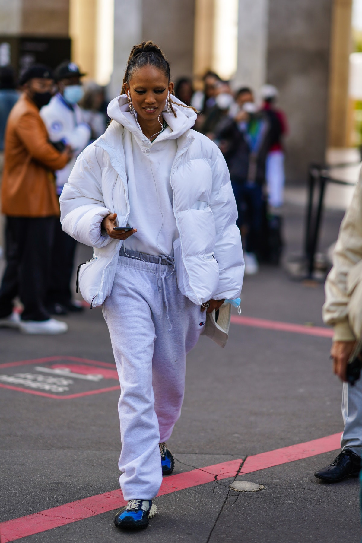 PARIS, FRANCE - OCTOBER 01: A guest wears earrings, a white hooded sweatshirt, a white puffer jacket, light blue sport pants with drawstring, blue and black sneakers, outside Chloe, during Paris Fashion Week - Womenswear Spring Summer 2021, on October 01, 2020 in Paris, France. (Photo by Edward Berthelot/Getty Images)