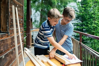 Little boys are building an easel from wood pieces. The boy is driving a screw into the wood with a ...