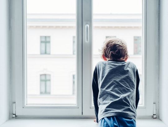 boy looking out the window alone