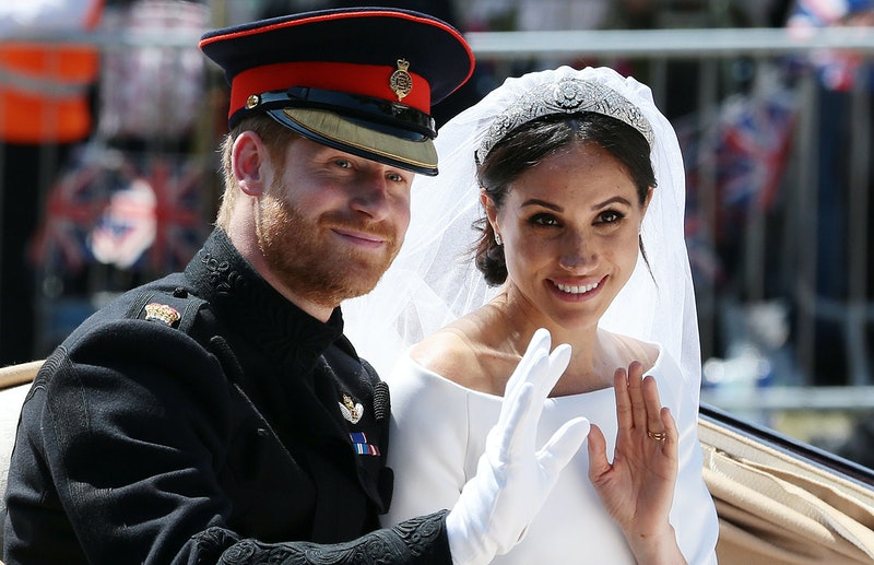 TOPSHOT - Britain's Prince Harry, Duke of Sussex and his wife Meghan, Duchess of Sussex wave from the Ascot Landau Carriage during their carriage procession on the Long Walk as they head back towards Windsor Castle in Windsor, on May 19, 2018 after their wedding ceremony. (Photo by Aaron Chown / POOL / AFP)        (Photo credit should read AARON CHOWN/AFP via Getty Images)