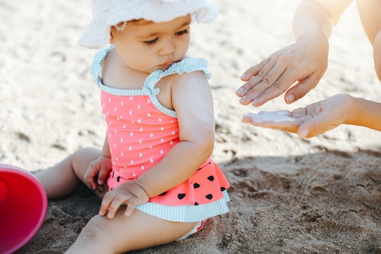Happy laughing toddler girl having fun on sand, mom applying sunscreen