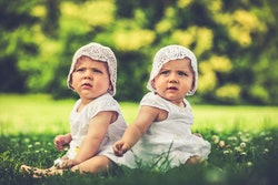 little baby twin sisters enjoying a summer day out in the green.