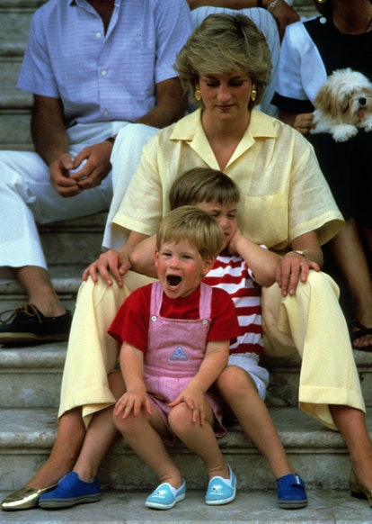 PALMA, MAJORCA - AUGUST 10: Diana, Princess of Wales, wearing a yellow jumpsuit, Prince William and Prince Harry sit on the steps of Marivent Palace with members of the Spanish Royal family on August 10, 1987 in Palma, Majorca. (Photo by Anwar Hussein/Getty Images)