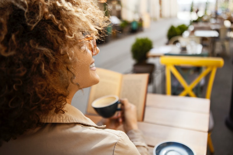 A woman drinks a cup of coffee outside; the caffeine makes her feel better.