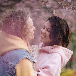 Two women hug in a cherry blossom garden. How long does it take to love someone? Experts explain why it's different for everyone.