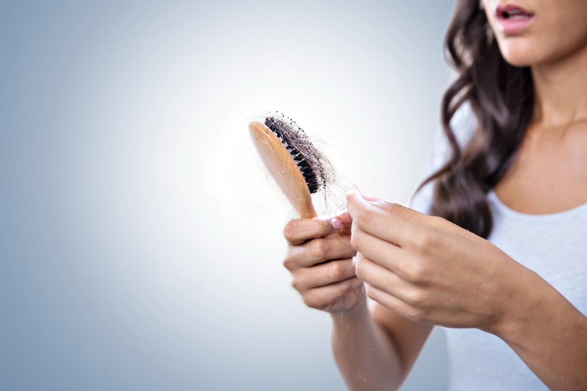 Worried woman holding hairbrush full of hair.
