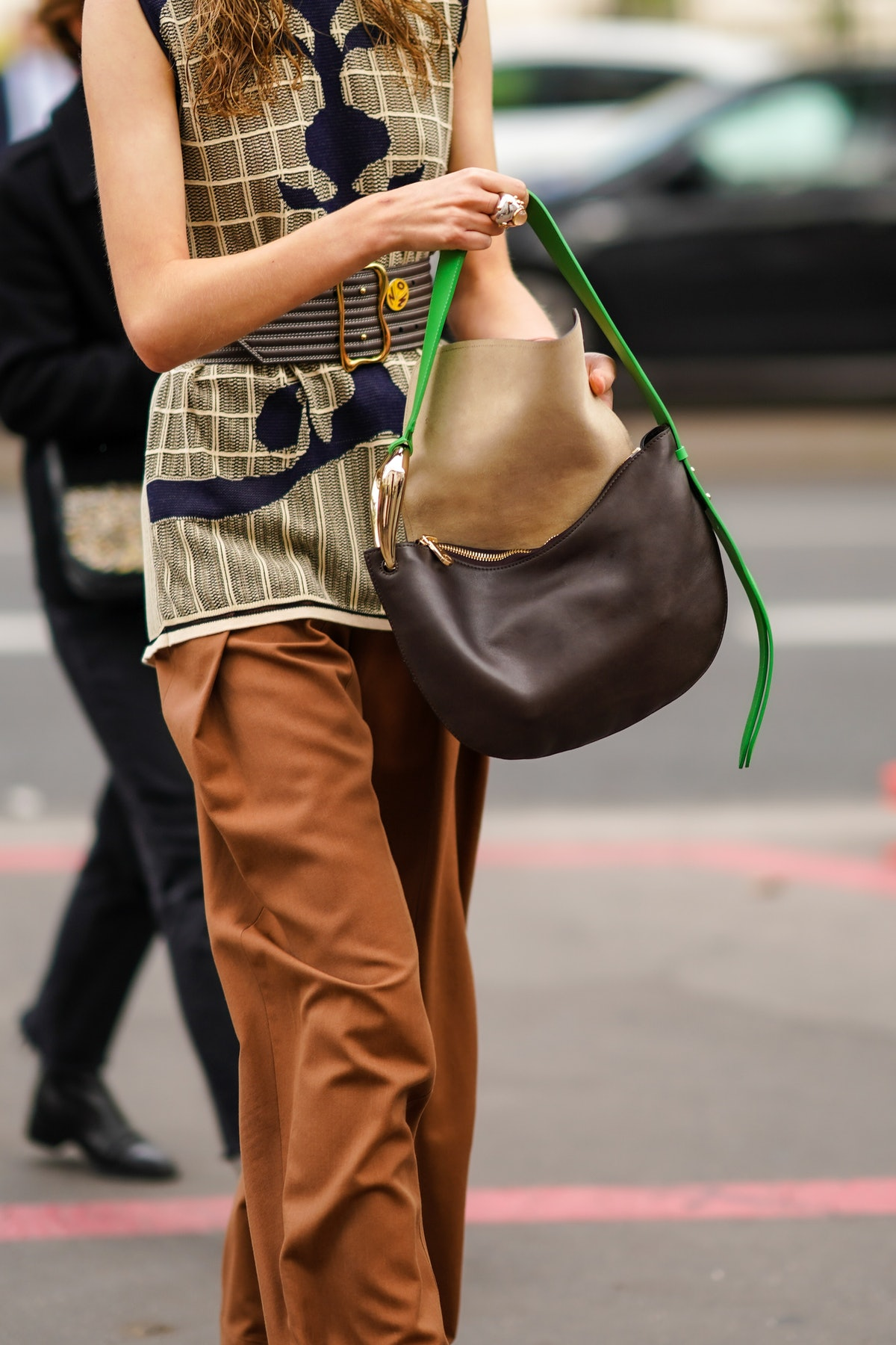 PARIS, FRANCE - OCTOBER 01: A guest wears a ring, bracelets, a  beige sleeveless top with black inserts, brown pants, a dark brown Chloe bag with a green strap, a large brown belt, outside Chloe, during Paris Fashion Week - Womenswear Spring Summer 2021, on October 01, 2020 in Paris, France. (Photo by Edward Berthelot/Getty Images)