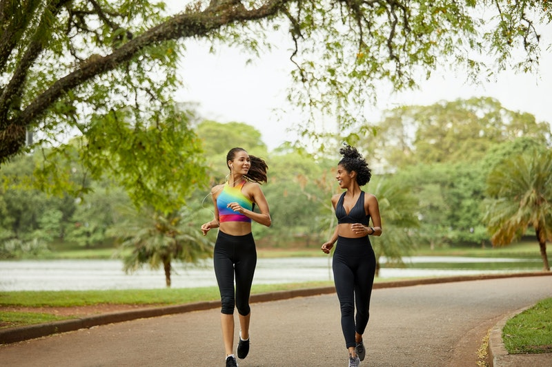 Smiling female looking at friend in park. Mid adult women are talking while jogging during summer. They are in sports clothing.