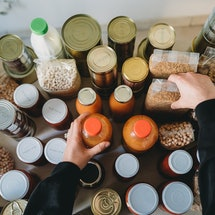 A woman arranges bottles and jars of foods you can eat past the expiration date.