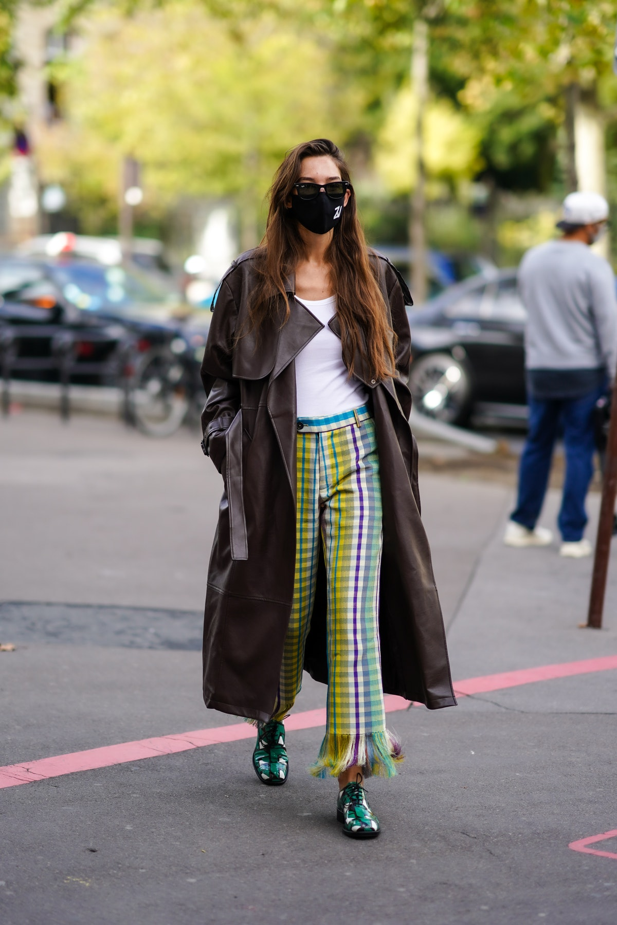 PARIS, FRANCE - OCTOBER 01: Estelle Chemouny wears black Ray Ban sunglasses, a black ZV logo face mask, a white t-shirt, a long brown shiny leather blazer jacket coat, yellow blue purple and white checkered flared ripped fringed pants, shiny green and white pattern lace derby shoes, outside Chloe, during Paris Fashion Week - Womenswear Spring Summer 2021, on October 01, 2020 in Paris, France. (Photo by Edward Berthelot/Getty Images)