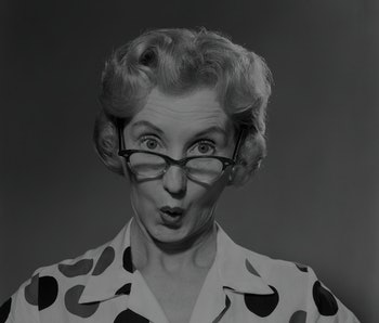 1950s 1960s PORTRAIT WOMAN POLKA DOT DRESS LOOKING AT CAMERA OVER EYEGLASSES  (Photo by Debrocke/ClassicStock/Getty Images)