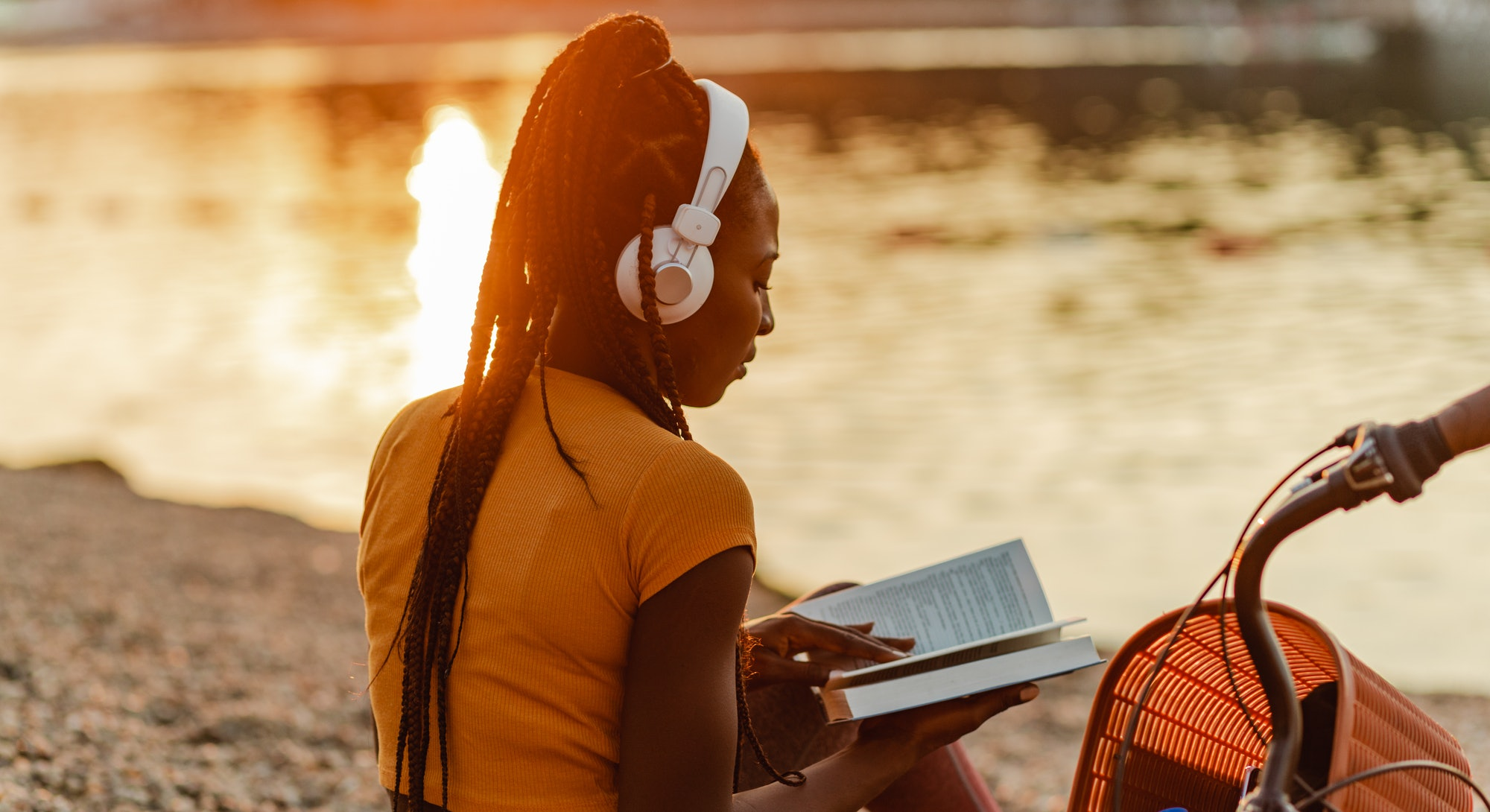 Photo of a young African American woman is using wireless headphones, she is sitting on the lakeshore next to her bicycle
