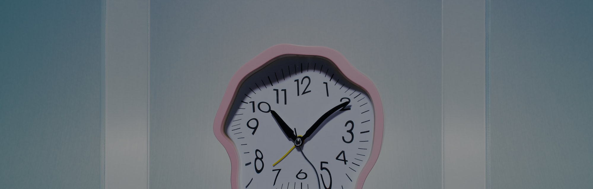 Melting pink analog clock in mid air inside of clear lucite cube