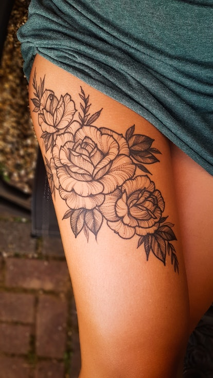 Black roses tattoo on a women's thigh part of the leg. with some leaves decoration. The woman wearing a green dress