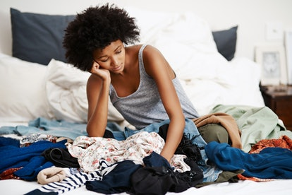 Shot of an unhappy young woman getting dressed with piles of clothing on her bed