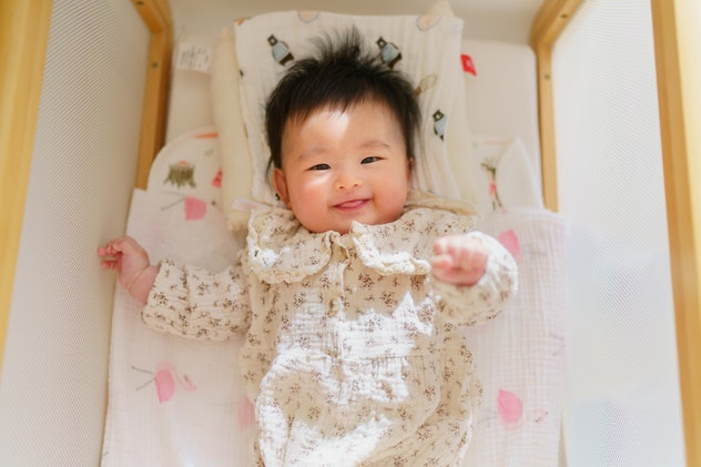 A portrait of a small baby looking at the camera and smiling.