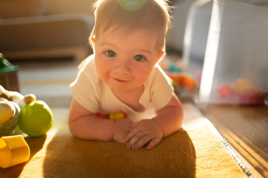 Portrait of a Caucasian baby boy with toys on the floor of his playroom looking at the camera.
