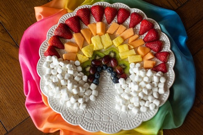 Fruit and marshmallows arranged in a rainbow.