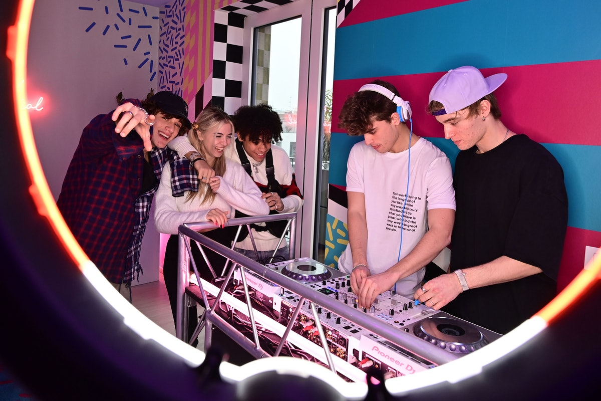 """(L-R) TikTok influencers Tommaso Donadoni, Alessia Lanza, Yusuf Panseri, Simone Berlini and Marco Bonetti play music in the """"Defhouse"""", a TikTok influencers incubator in Milan, on January 21, 2021. - With dreams of the big screen but Internet in their veins, eight young Italian influencers are racking up followers as they spend their days in a Milan TikTok luxury loft. All the influencers live on site -- although the youngest still go to school -- where they receive training in a variety of areas potentially of use in their videos, whether music and culture, politics and current affairs, diction, or even good manners. (Photo by MIGUEL MEDINA / AFP) (Photo by MIGUEL MEDINA/AFP via Getty Images)"""