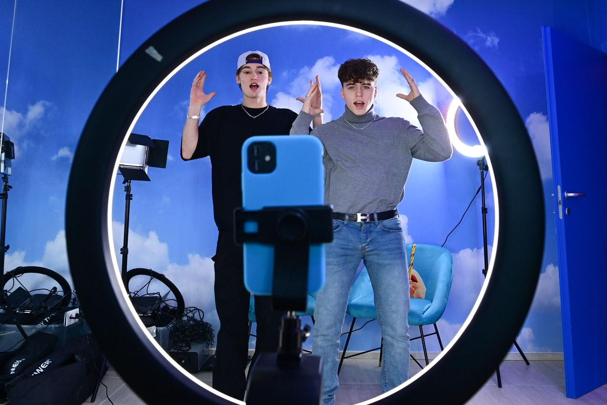 """(L-R) TikTok influencers Marco Bonetti and Davide Moccia perform a video in the """"Defhouse"""", a TikTok influencers incubator in Milan, on January 21, 2021. - With dreams of the big screen but Internet in their veins, eight young Italian influencers are racking up followers as they spend their days in a Milan TikTok luxury loft. All the influencers live on site -- although the youngest still go to school -- where they receive training in a variety of areas potentially of use in their videos, whether music and culture, politics and current affairs, diction, or even good manners. (Photo by MIGUEL MEDINA / AFP) (Photo by MIGUEL MEDINA/AFP via Getty Images)"""
