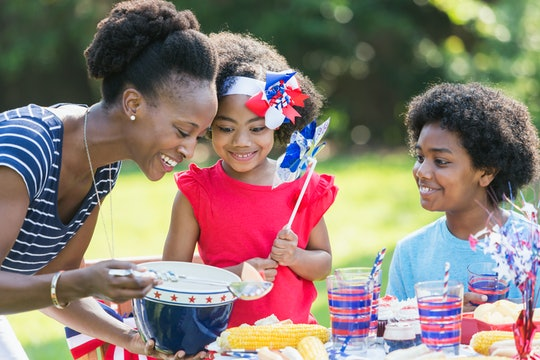 An African American mother with two mixed race children celebrating an American patriotic holiday, perhaps July 4th or Memorial Day. They are having a back yard cookout, sitting at a table decorated in red, white and blue.
