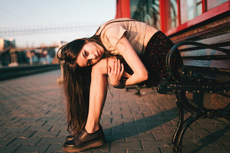 woman sitting in fetal position on a bench