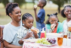 Two African-American adult sisters in their 30s with their three children at a backyard cookout. The children are mixed ages, 3 through 10 years old. The focus is on the mother and 3 year old boy eating into a hot dog.