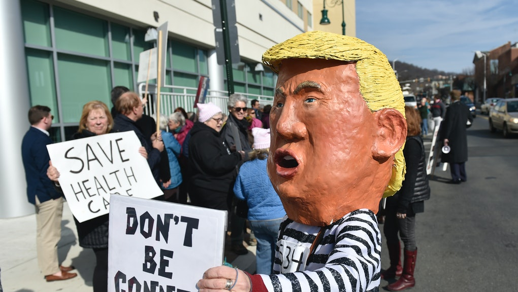 """A protester in a Donald Trump costume holds a sign reading """"Don't be conned"""". At the DoubleTree Hotel in Reading Monday afternoon Feb. 6, 2017 where the Greater Reading Chamber of Commerce held it's annual meeting with the Berks County Congressional Delegation (Congressmen Lloyd Smucker, Ryan Costello, Pat Meehan, and Charlie Dent.) Protestors gathered outside of the hotel, and later in a conference room where they invited the lawmakers to join them for a town hall meeting. None of the Congressmen took them up on the offer. Photo by Ben Hasty (Photo By Ben Hasty/MediaNews Group/Reading Eagle via Getty Images)"""