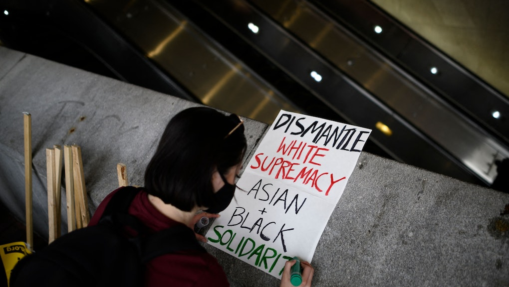 A woman makes a sign before an 'Anti Asian Hate' rally in Chinatown in Washington, DC on March 27, 2021. - The rally comes on the heels of last weeks shooting deaths of six women of Asian descent at multiple massage parlors in the Atlanta area. (Photo by ANDREW CABALLERO-REYNOLDS / AFP) (Photo by ANDREW CABALLERO-REYNOLDS/AFP via Getty Images)