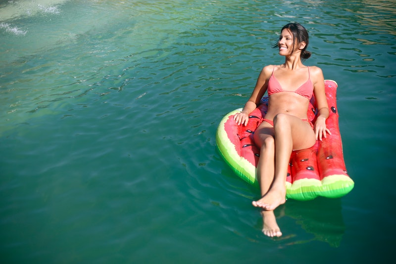 Young woman relaxing on an air mattress at a pool.  About 25 years old, Caucasian brunette.