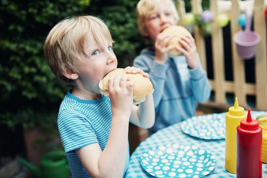 Two little boys eating burgers at a family barbecue