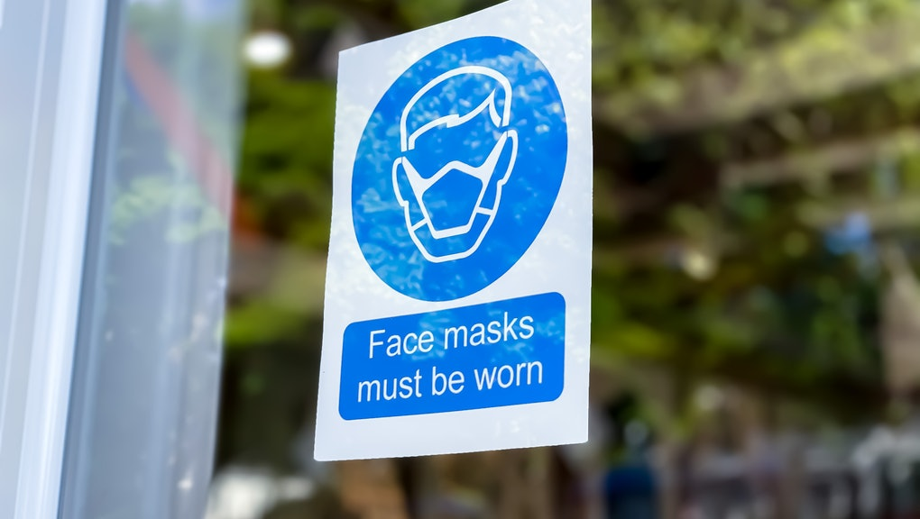covid-19 mask required sign posted on retail store door