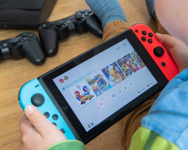 31 March 2020, Lower Saxony, Hanover: ILLUSTRATION - A child is playing with a Nintendo Switch game console while a Sony Playstation 3 with two controllers is seen in the background (scene posed) Because of the contact restrictions in the Corona crisis, criminologist Christian Pfeiffer sees a significantly increased risk of video and computer game addiction among children and adolescents. Photo: Julian Stratenschulte/dpa (Photo by Julian Stratenschulte/picture alliance via Getty Images)