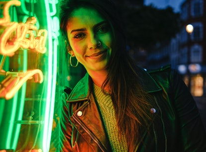 Happy young woman illuminated in green neon amid the new moon solar eclipse.