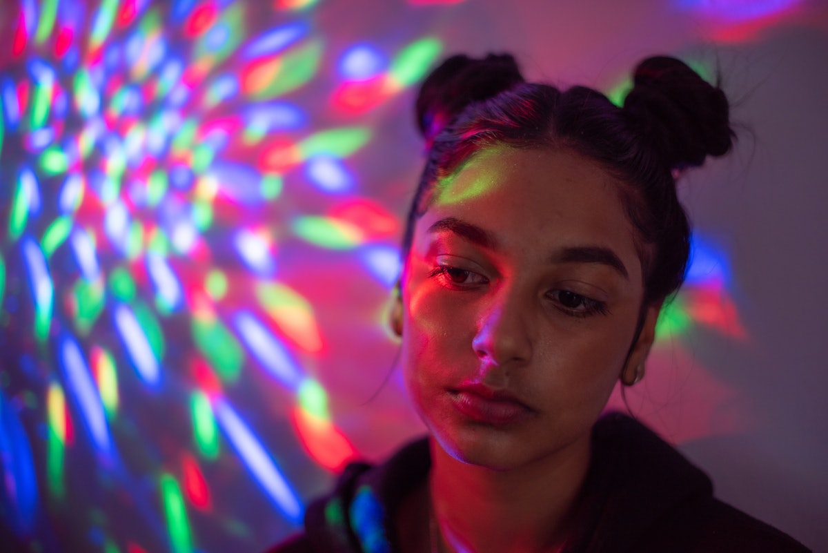 Sad young woman in neon lights amid the June 2021 new moon solar eclipse.