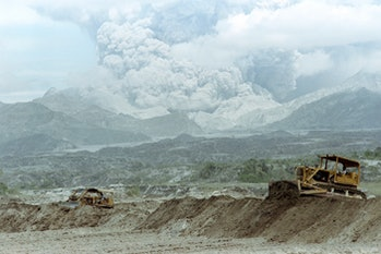 Bulldozers rush to repair collapsed Taug Dike, on June 29, 1991 as lake of trapped volcanic mudflow lies on the slopes of Mount Pinatubo volcano about 16 kilometers away. The eruption of Mount Pinatubo on June 15, 1991 was the second largest volcanic eruption of the twentieth century. (Photo by ROMEO GACAD / AFP) (Photo by ROMEO GACAD/AFP via Getty Images)