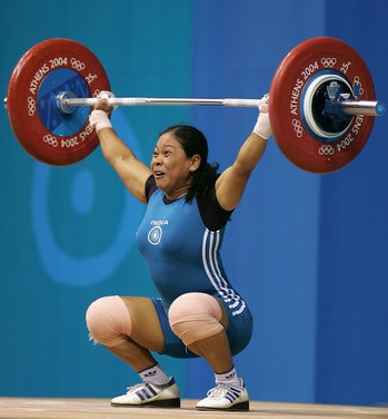 ATHENS - AUGUST 15:  Thingbaijam Sanamacha Chanu of India competes in the women's 53 kg category weightlifting competition on August 15, 2004 during the Athens 2004 Summer Olympic Games at Nikaia Olympic Weightlifting Hall in Athens, Greece. (Photo by Mark Dadswell/Getty Images)