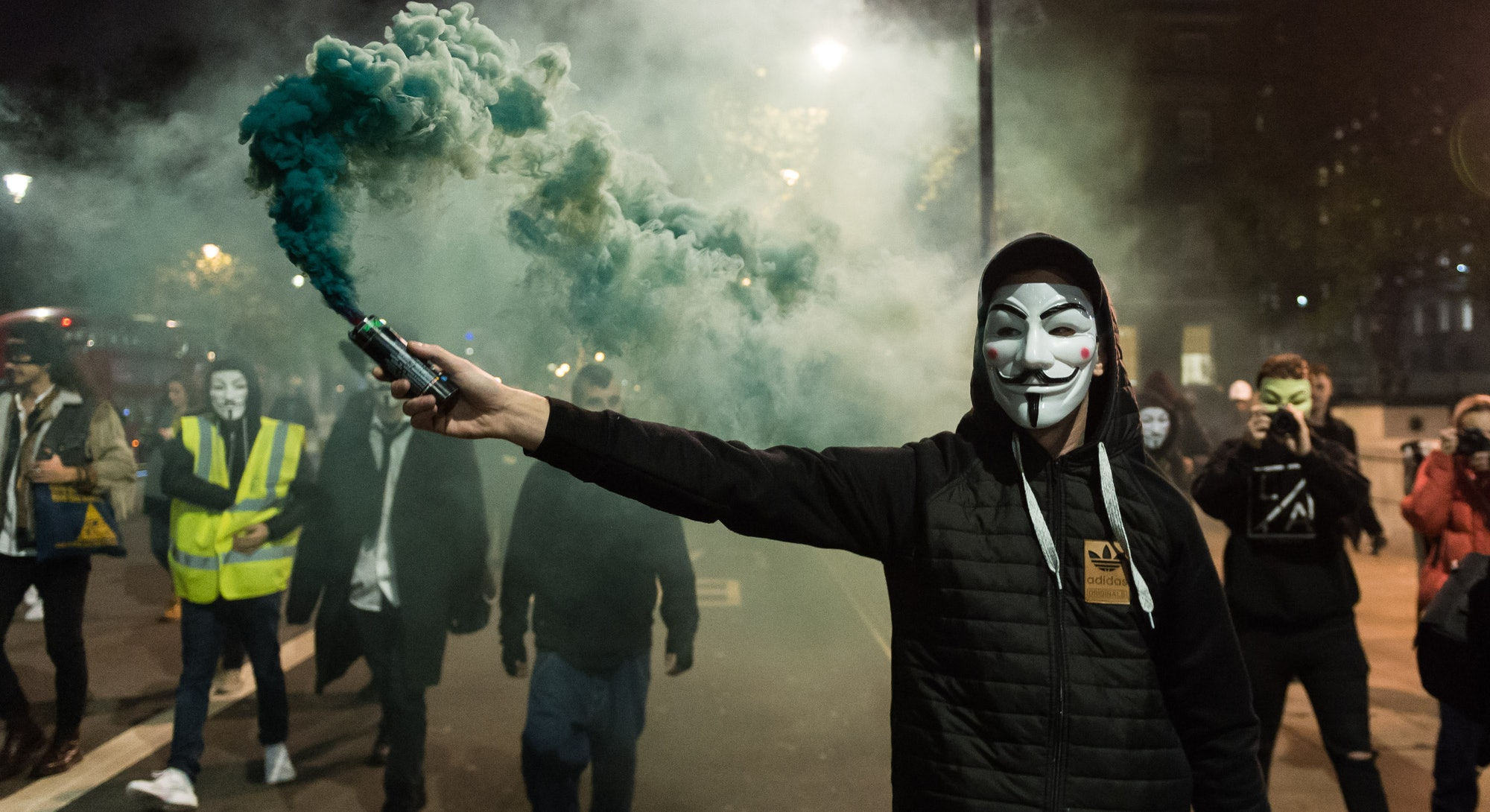 LONDON, UNITED KINGDOM - NOVEMBER 5: Demonstrator wearing Guy Fawkes mask sets of a smoke bomb as hundreds take part in the annual 'Million Mask March' on Bonfire Night. The event is a part of a global anti-establishment and anti-capitalist protest against issues such as austerity, infringement of human rights, surveillance, politics and economics. November 5, 2018 in London, England. (Photo credit should read Wiktor Szymanowicz / Barcroft Media via Getty Images)