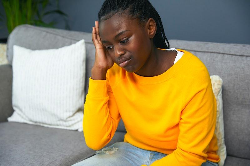Sad teenage girls sitting on a sofa in her living room
