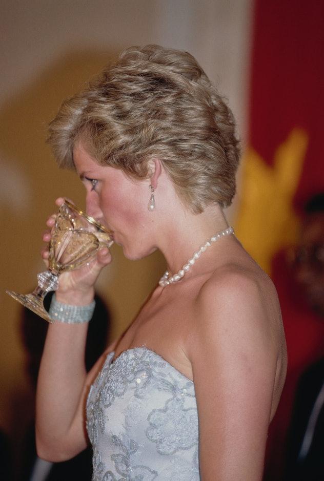 Princess Diana enjoys a cocktail.
