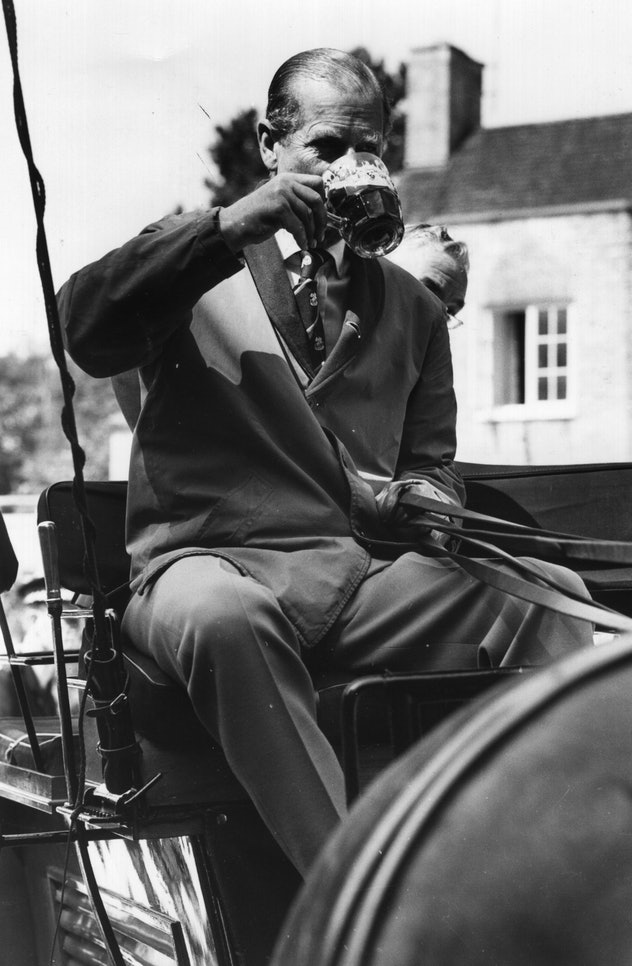 Prince Philip drinks a beer while driving a carriage.