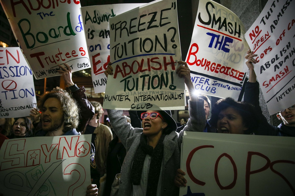 Students hold signs as they stage a demonstration against student debt at Hunter College in New York City.