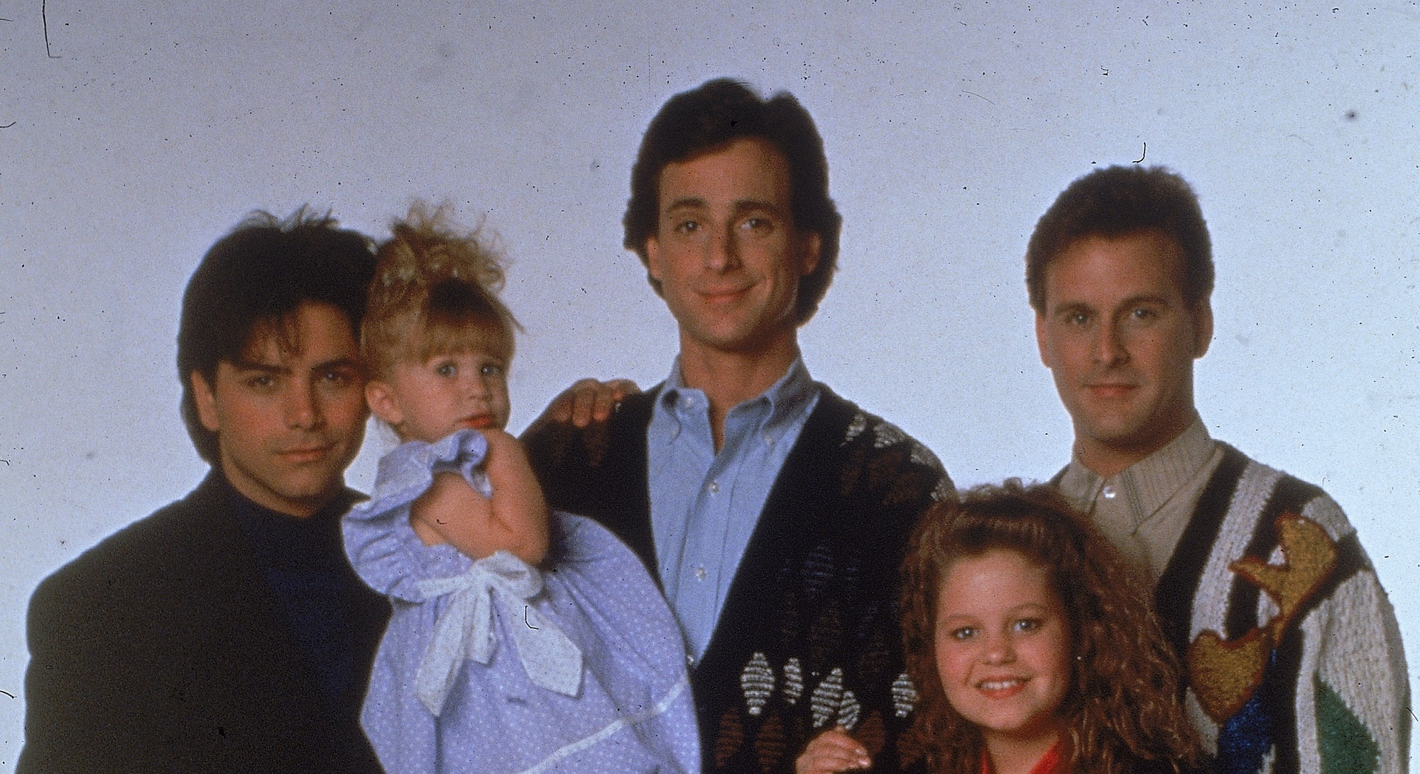 Portrait of the cast of the television program, 'Full House,' (left - right): John Stamos, Jodie Sweetin, Ashley or Mary-Kate Olsen, Bob Saget, Candace Cameron, and David Coulier, c. 1989. (Photo by Fotos International/Getty Images)