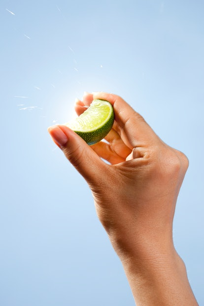 Asian woman squeezing a lime slice between her fingers with the blue sky and sunburst in the backgro...