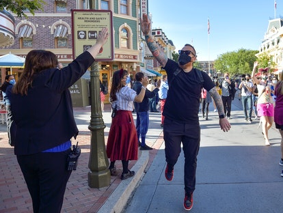 "Anaheim, CA - April 30: A visitor to Disneyland high-fives employees as he walks up Main Street U.S.A. just after the gates opened in Anaheim, CA, on Friday, April 30, 2021. The resort""u2019s parks have been closed for 412 days due to the COVID-19 outbreak. (Photo by Jeff Gritchen/MediaNews Group/Orange County Register via Getty Images)"