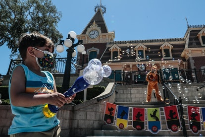 Anaheim, CA, Friday, April 30, 2021 - Mathew Jimenez, 2, of Santa Fe Springs, blows bubbles with Pluto on Main Street as a limited number of people come to Disneyland the first day after closing more than a year ago.  Characters remained distanced from guests, not getting close enough for hugs and handshakes. (Robert Gauthier/Los Angeles Times via Getty Images)